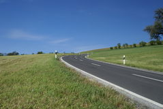 Country road in Switzerland. Road leading through a grass landscape in Switzerland Stock Image