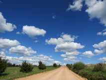 Country Dirt Road, Bright Blue Sky and Puffy White Clouds Stock Photo