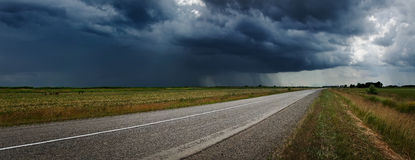 Country road and thunderstorm on a background. Some minutes before the beginning of a pouring rain and a strong wind Krasnodar Territory, North-Western Royalty Free Stock Photos