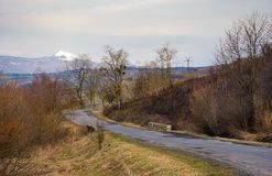 Country road in to the mountains with snowy peak. Lovely transportation background in springtime Stock Images