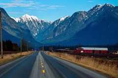 Country Road to Pitt Lake. A country road of the Pitt River Valley runs through farm fields and forest to  Pitt Lake on the background of the snow-covered stock images
