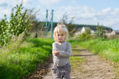 Seriouse blond boy staying embraced himself with his arms. Country road to the Urals village, Russia Royalty Free Stock Photos