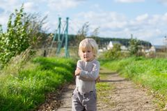 Seriouse blond boy staying embraced himself with his arms. Country road to the Urals village, Russia Royalty Free Stock Photography