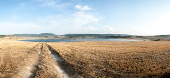 Country road towards the lake in Navarra, Spain. Quiet and peaceful landscape in Navarra. The road leads to the lake, around the fields and a calming landscape royalty free stock photo