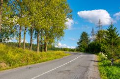 Country road uphill in to the forest. Lovely autumn scenery. travel by car concept Royalty Free Stock Photo