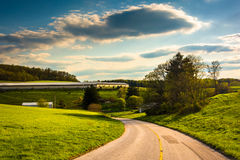Country road and view of farm fields and rolling hills in rural Stock Image