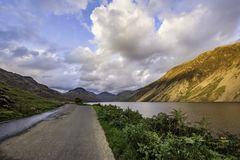 Country road with view on scenic valley in Lake District,Cumbria,Uk. Country road with view on scenic valley with lake, sunlight kissing hill slope and blue sky royalty free stock photo