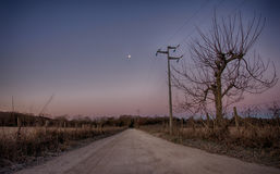 Country road with waning moon Stock Images