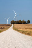 Country road and a wind farm Royalty Free Stock Photos
