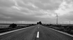 Country road and a wind farm. A country gravel road leading to large wind turbine on a windfarm Royalty Free Stock Photo