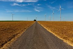 Country road with wind turbines in blu. Beautiful country road with white wind turbines with red stripes generating electricity on a bright blue cloudy sky royalty free stock image