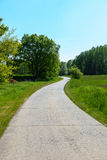 Country Road. Winding country road through green fields and forests in the German countryside in Spring Stock Photo
