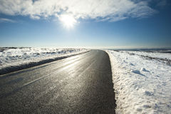 Country road through winter rural scene Royalty Free Stock Image