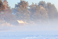 Country sauna and a winter fog over the frozen river. A sudden fog on a cold day Stock Images