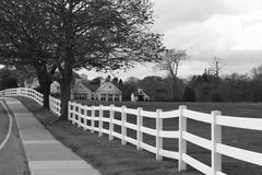 Country scene. White fence surrounding a horse pasture with home and barn in the distance in black and white Stock Image