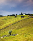 Country scene with wooden huts on the hill and sky rain Royalty Free Stock Photos