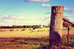 Country side scene with old gate post and barb wire Royalty Free Stock Image