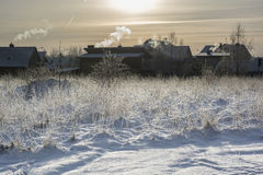 Country side winter landscape. Cold snowy winter landscape in village. Multiple houses with smoke Royalty Free Stock Image