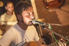 Country singer sings in a bar. Under the dim lights royalty free stock photography