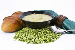 Country Split Pea Soup and Fresh Bread. Split pea soup in black bowl with fresh loaf of bread, green napkin and brown wood napkin ring on dried  peas ingredient Stock Photography