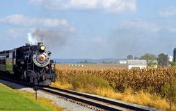 Country steam locomotive. A view of an authentic coal-burning steam locomotive or engine pulling an 18th century train through farming country and cornfields on Royalty Free Stock Photography