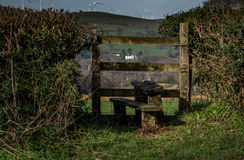 Country stile. Image of a country stile dappled with sunlight on a spring morning. Beyond the stile a white house in the distance on a mountain topped with the Royalty Free Stock Image