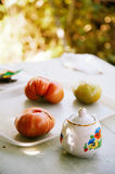 Country still life. Tomatoes and a sugar bowl on the wooden table Stock Photography