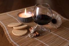 Country still life biscuit,and spices. A glass of wine, cinnamon, pine cone and a burning candle Stock Photography