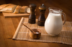 Country still life, white bread, milk jug and spices. Country still life. Pitcher of milk on a wooden table Royalty Free Stock Image