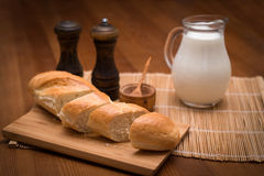 Country still life, white bread, milk jug and spices. Country still life. Pitcher of milk on a wooden table Stock Photos