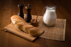 Country still life, white bread, milk jug and spices. Country still life. Pitcher of milk on a wooden table Stock Photo