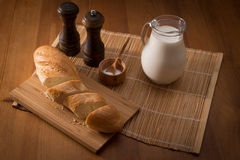 Country still life, white bread, milk jug and spices. Country still life. Pitcher of milk on a wooden table Stock Images