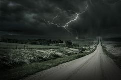 Country Storm. Back Country Gravel Road and Storm Ahead. Lightning Bolt in a Distance. Severe Weather Collection stock photography