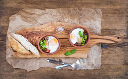 Country style breakfast set. Eggs baked in separate clay cups with tomatoes, peppers, fresh basil, bread slices on Stock Photos