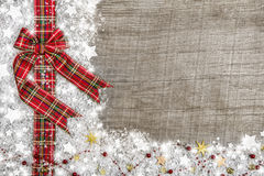 Country style christmas background with red green checked ribbon. On wood with snow and golden stars. Idea for a frame or billboard Stock Images