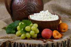 Country style. Cottage cheese in a clay dish, grape, apricots on wooden background. Royalty Free Stock Photo