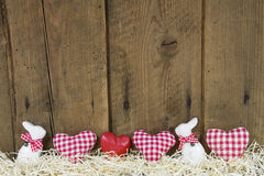 Country style easter wooden background with red checked hearts.
