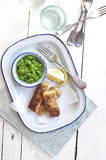 Country style fish fingers. Fish fingers with peas purée and lemon on blue rim enamel plate and rustic wooden table royalty free stock image