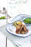 Country style fish fingers. Fish fingers with peas purée and lemon on blue rim enamel plate and rustic wooden table royalty free stock photos
