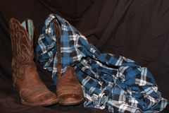Country Style. Flannette shirt draped over cowboy boots, the wardrobe of a true country man or woman royalty free stock photography