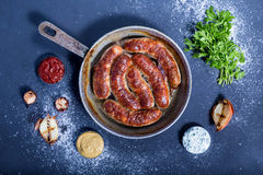 Country style oven-baked sausages in a frying pan Royalty Free Stock Images