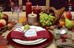 Country style rustic Thanksgiving table setting. Country style rustic Thanksgiving table with place setting, cornucopia, candles and Autumn fruit centerpice Royalty Free Stock Image