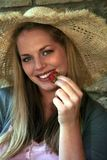 Country Style Strawberry Blond Girl. Image of a blond model in a straw hat eating a fresh strawberry, conceptual health and country living stock photos