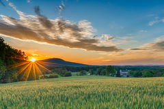 Country Sunset. A perfect Spring day ends as the sun sets and sprays warm golden light over a beautiful farm with fields sprouting, a stone house, and mountain royalty free stock image