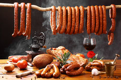 Country table with meat, wine and smoke. Country table with many kinds of ham and sausage, with  wine, spices and smoke Royalty Free Stock Photo
