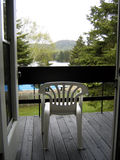 Country vacation morning. Plastic chair on the country inn's balcony overlooking green forest mountains and lake Stock Photography