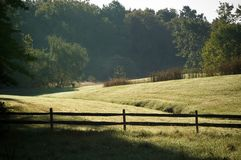 Country View. View of a field in the country including a split rail fence surrounding a field.  Deer are visible in the distance near the trees on the left of Stock Photo