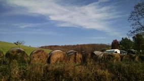 Country View. View of field in the fall looking over the round bales of hay with a beautiful blue sky Royalty Free Stock Image
