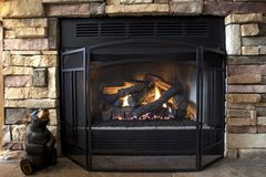 Country Warmth. A gas log fireplace provides both emotional and physical warmth as the afternoon sun streams in on a cold winter day stock photos