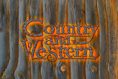 Country and Western. Rustic type treatment of the title banner Country and Western in hammered metal with orange glow suggesting a hot branding iron Royalty Free Stock Photo